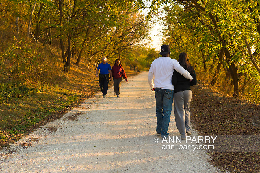 South Merrick, New York, U.S. 29th October 2013. JIMMY EDWARDS, of Bellmore, and TAMI BAQUE, of Freeport, both seen from behind, walk on the trail through Levy Park and Preserve during dusk, on the First Anniversary of Superstorm Sandy hitting New York. Long Island's South Shore marshland park, which closed for months due to Sandy's devastation, shows some recovery from the wind and flood damage inflicted on the entire eastern seaboard of America's East Coast.