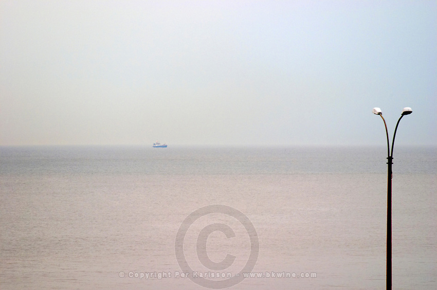 A view over the Rio de la Plata in Montevideo on a rainy day, fog rain and haze making it a gray day, a ship on the horizon and a lamp post Rambla sur and Rambla Gran Bretagna along the River Rio de la Plata Montevideo, Uruguay, South America