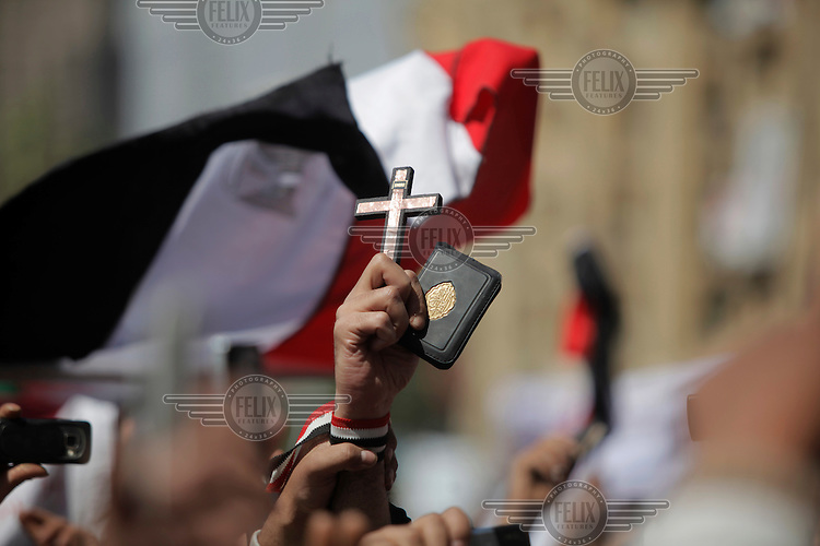 A man holding a cross and a Qur'an. Christians and Muslims came together on Friday prayers in Tahrir square, advocating peaceful co existence. Sectarian violence had flared in the wake of the revolution that saw president Hosni Mubarak removed from office.