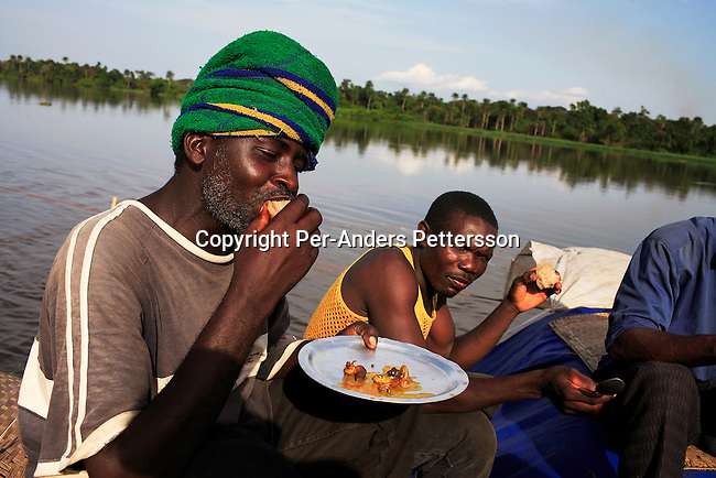 BUMBA, DEMOCRATIC REPUBLIC OF CONGO APRIL 7: Kogbau Yenge (l), age 40, eats snails and bread on April 7, 2006 in Bumba, Congo, DRC. He is a trader and is traveling to Kinshasa to sell maize. In Kinshasa he will buy shoes, clothes etc, to sell in his village on his return. Snails are priced 50 cents for seven pieces. Passengers usually sleep in the open, often on top of maize bags or other cargo. The boat carries many animals such as pigs, goats, crocodiles, monkeys, lizards, etc. The Congo River is a lifeline for millions of people, who depend on it for transport and trade. The journey from Kisangani to Kinshasa is about 1750 kilometers, and it takes from 3-7 weeks on the river, depending on the boat. During the Mobuto era, big boats run by the state company ONATRA dominated the traffic on the river. These boats had cabins and restaurants etc. All the boats are now private and are mainly barges that transport goods. The crews sell tickets to passengers who travel in very bad conditions, mixing passengers with animals, goods and only about two toilets for five hundred passengers. The conditions on the boats often resemble conditions in a refugee camp. Congo is planning to hold general elections by July 2006, the first democratic elections in forty years..(Photo by Per-Anders Pettersson/Getty Images).
