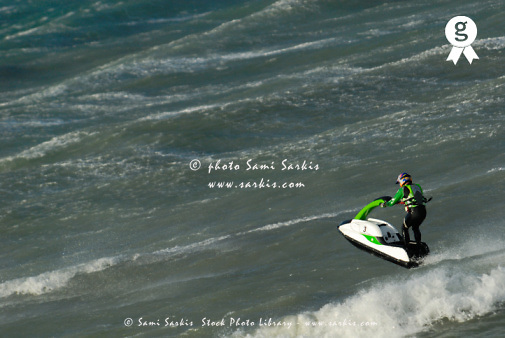 Man jumping on waves with jet-ski, elevated view (Licence this image exclusively with Getty: http://www.gettyimages.com/detail/sb10065474dj-001 )