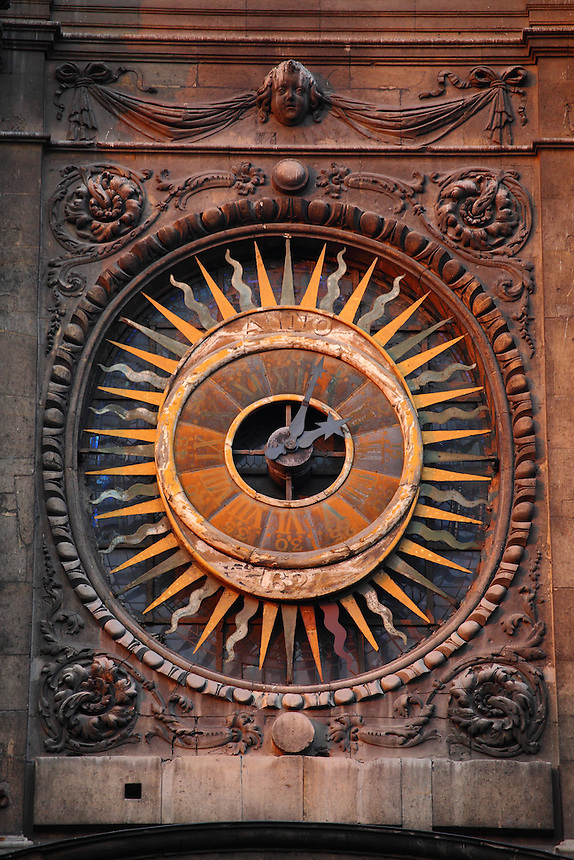 The ancient clock on the front of the Saint Paul and Saint Louis church of the Marais in Paris, slightly enlightened at the sunrise. Digitally Improved Photo.