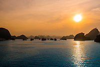 Sunset, Halong Bay, North Vietnam. The bay features 3,000  limestone and dolomite karsts and islets in various shapes and sizes sprinkled over 1,500 square kilometers. It offers a wonderland of karst topography. It is a UNESCO World Heritage Site.