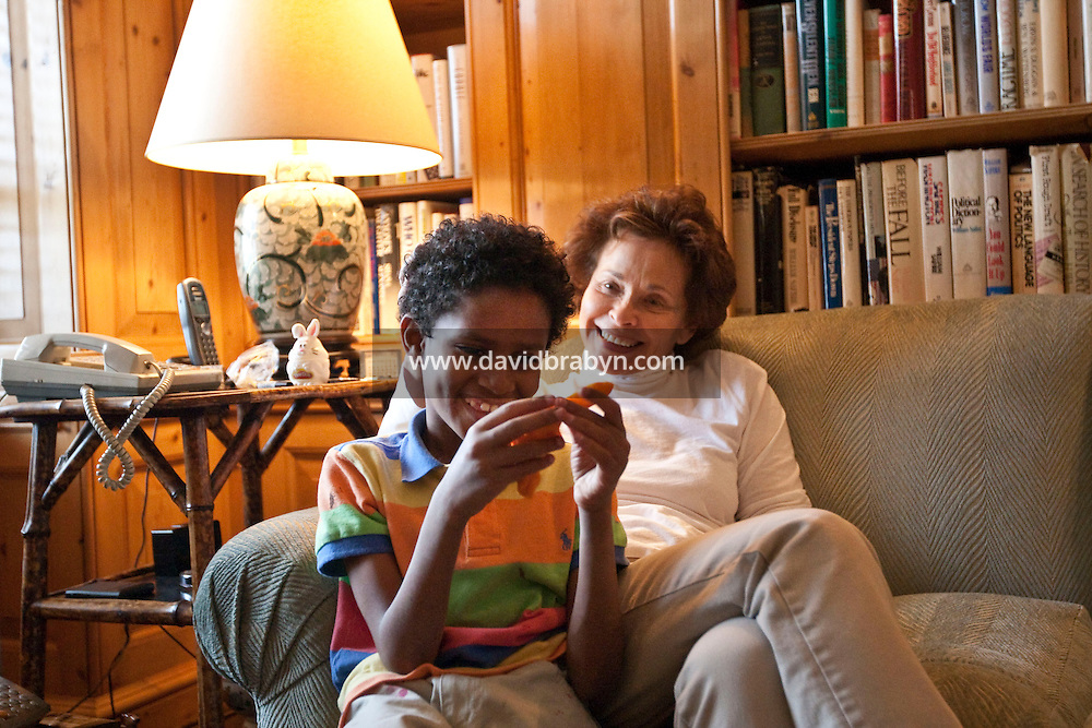 Marilyn Berger (R), widow of Don Hewitt, and Danny Hodes, the 8 year-old Ethiopian boy she has taken in, laugh together in her apartment in New York, NY, USA, 9 April 2010. Ms Berger met him in Addis Ababa while reporting there and helped him get surgery.