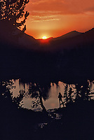 Man fishes at sunset on a lake in the High Sierras.