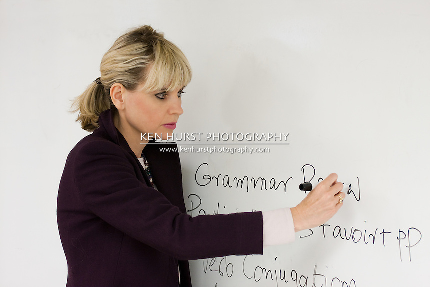 Woman teacher or instructor in a college, university, high school, middle school, elementary classroom writing on a white board with a marker pen.