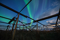 Northern Lights shine in sky over empty stockfish drying racks, Ballstad, Vestvågøy, Lofoten Islands, Norway
