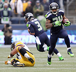 Seattle Seahawks running back Thomas Rawls (34) runs past Pittsburgh Steelers defensive end Stephon Tuitt (91) at CenturyLink Field in Seattle, Washington on November 29, 2015.  The Seahawks beat the Steelers 39-30.      ©2015. Jim Bryant Photo. All Rights Reserved.