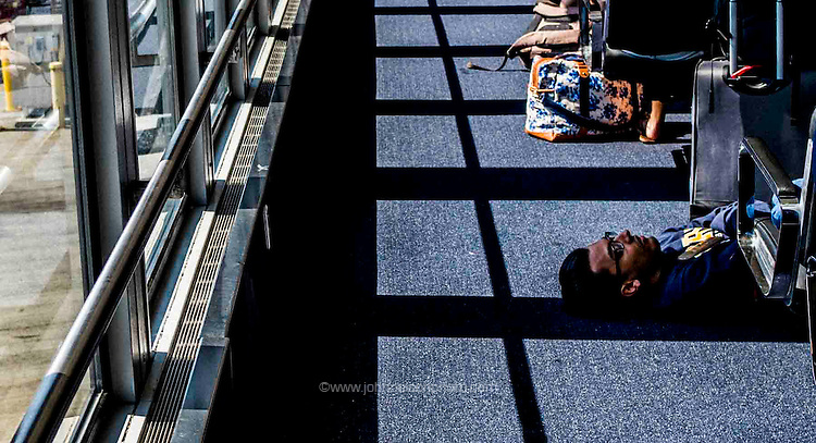 From the shadows, adventure and the unknown lightens the life of the weary traveler, Salt Lake City airport,<br /> #intransit #lifeontheroad #travel #airport #photojournalism #OlympusPenF
