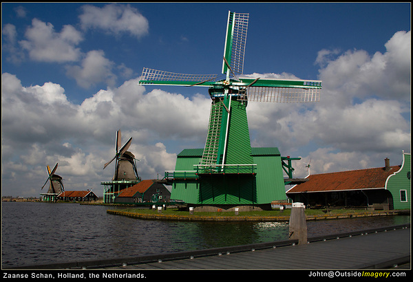 Netherlands, Zaanse Schans Windmills.<br /> When you have a great sky, look for a subject to put under it. Conversely, the windy lake provides only a dark surface and should be minimized. The diagonal walkway also helps to reduce the size of the lake.