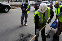 John Mullaney (center), temporary supervisor for construction for the Boston Public Works Department, takes a photo of repair work done by David Dollosa (left) and Lionel Hampton in Boston, Massachusetts, USA, on April 12, 2012.  The city uses a computer system to track public complaints and record work done by city crews to mitigate these complaints.  A supervisor or inspector photographs before and after pictures of the work in addition to making notes about the work done.