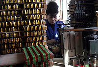 Surrounded by stcks of just-finished harmonicas, a worker assembles harmonicas with a simple machine at the Shanghai General Harmonica Factory (SGHF) in Shanghai, China. Although it makes well-respected brands such as the Huang, Suzuki, and Hohner that are favored by many professional musicians around the world, the 60 years old state owned SGHF had to trim down its work force from 800 in the mid 1980's to just over 100 today. These workers churn out an average of 1900 harmonicas a day..23-FEB-04