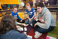 Salve Regina volunteer Jake Williams, '15, right, Cathryn Blair,'18, and Genna Hoyt,'18, works with children on language skills at the Pell School in Newport as part of a Modern Languages Program.