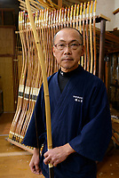 Reimei Yokoyama with a bow. Yokoyama Reimei Bowmakers, Miyakonojo, Miyazaki Prefecture, Japan, December 23, 2016. A handful of bowyers from the Kyushu city of Miyakonojo make over 90% of all the bows used in traditional Japanese archery. The bows are made from laminated bamboo and haze wood in process that consists of over 200 individual tasks. At over two meters from tip to tip the bows the longest used in the world.