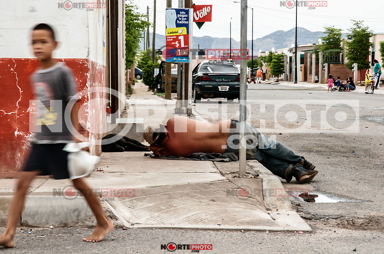 Un niño que camina por al calle  Lázaro Mercado y Avenida ASH en el fraccionamiento Floresta. Indigente dormido en la baqueta. Acera. Alcolito. Acolico, Alcholismo. Alchool.