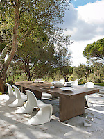 White Arne Jacobsen chairs are placed around a wood table on a terrace area providing an outside dining space, which overlooks a garden planted with oaks.