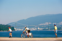 Stanley Park, Vancouver, BC, British Columbia, Canada - Family cycling and rollerblading on Seawall along Burrard Inlet in Summer - Lions Gate Bridge, West Vancouver, and North Shore Mountains in background
