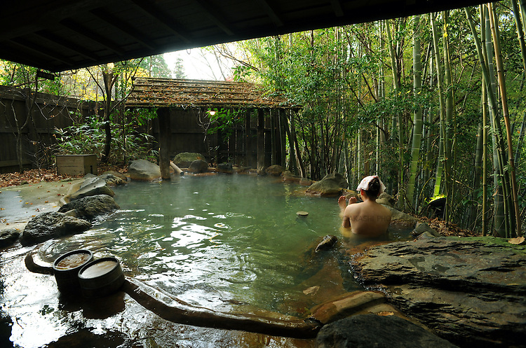 A Japanese woman takes a bath in Robenburo, outdoor bath, surrounded by bomboo in Kurokawa onsen hot spring.