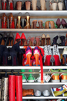 Shelves of multi-coloured shoes and boots of all shapes and designs line one wall of Sacha's walk-in wardrobe