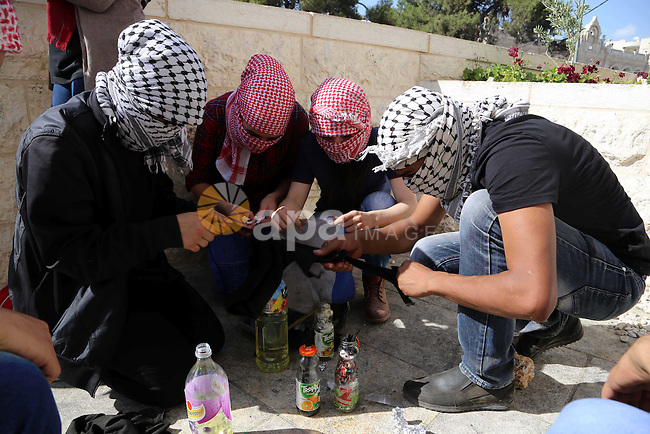 Palestinian protesters prepare molotov cocktails during clashes with Israeli troops in the West Bank city of Bethlehem October 14, 2015. Seven Israelis and 30 Palestinians, including children and assailants, have been killed in two weeks of bloodshed in Israel, Jerusalem and the occupied West Bank. The violence has been partly triggered by Palestinians' anger over what they see as increased Jewish encroachment on Jerusalem's Al-Aqsa mosque compound. Photo by Muhesen Amren