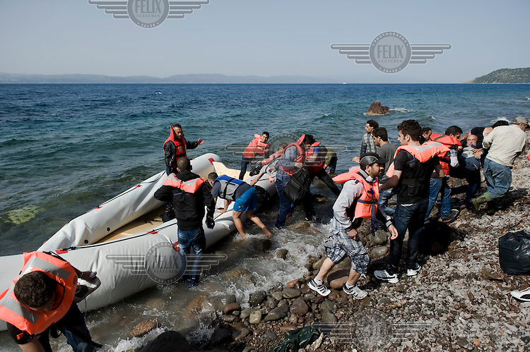 A group of Syrian refugees disembark from their small inflatable boat and land on the beach of Skala Sykaminias on the Greek island of Lesbos. <br /> Every day hundreds of refugees, mainly from Syria and Afghanistan, are crossing in small overcrowded inflatable boats the six mile channel from the Turkish coast to the island of Lesbos in Greece. Many spend their life savings, over $1,000, to buy a space on these boats.