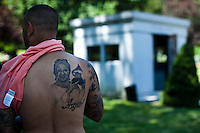 A fan shows his tattoo of the queen of salsa Celia Cruz at her mausoleum during her 10th death anniversary in the Bronx in New York,  July 13, 2013. Photo by Eduardo Munoz Alvarez / VIEWpress.