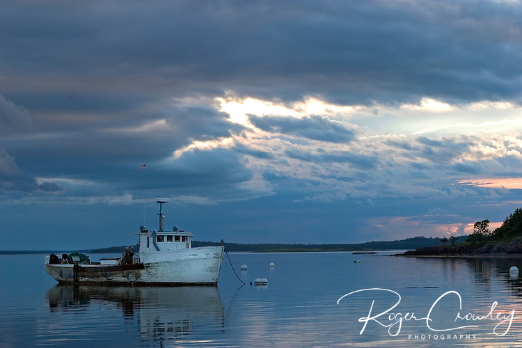 Roger Crowley / CrowleyPhotos.com..A fishing boat sits idle at sunset off the coast of Maine..