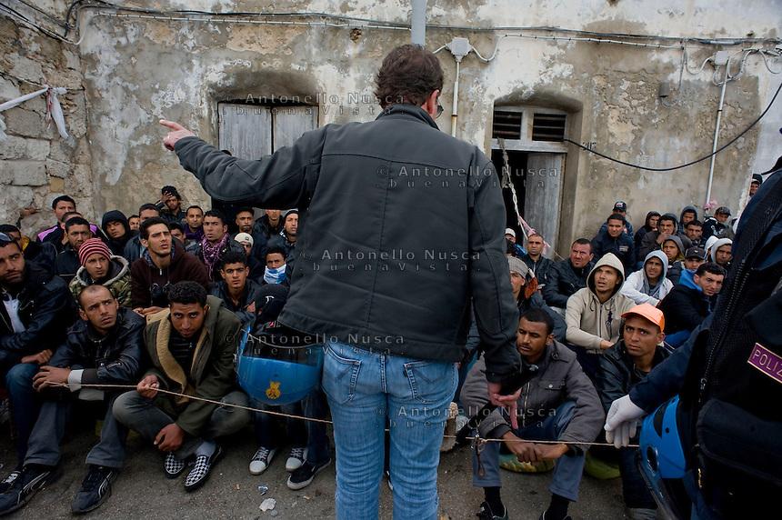 Immigrati Tunisini vengono controllati dalla Polizia per l'identificazione prima di essere trasferiti nei centri di accoglienza. Tunisian immigrants are checked by Italian police before boarding a cruise liner to a different part of Italy, on the southern island of Lampedusa.