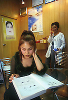 Eighteen-year old Ms. Xue underwent eye and nose surgery. She is now considering having more operations and studies a catalogue at an illegal cosmetic surgery clinic, Shenzhen, China. As the Chinese population grows richer more and people are turning to cosmetic surgeons for nose, eye and breast jobs...PHOTO BY SINOPIX