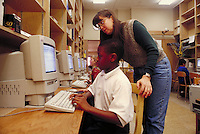 ELEMENTARY SCHOOL COMPUTER LAB. TEACHER GIVES INDIVIDUAL HELP TO STUDENT. ELEMENTARY STUDENTS. OAKLAND CALIFORNIA USA CARL MUNCK ELEMENTARY SCHOOL.