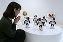 "A woman looks at communication robots called ""Robi"" dance during a press preview for ""Robi cafe"" where visitors can interact with the robots while enjoying meals and drinks in Tokyo, Thursday, January 15, 2015. The robot can be built by assembling parts sent along with a weekly magazine by Deagostini. The cafe will open from January 16 until February 8. (Photo by Yuriko Nakao/AFLO)"