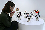 """A woman looks at communication robots called """"Robi"""" dance during a press preview for """"Robi cafe"""" where visitors can interact with the robots while enjoying meals and drinks in Tokyo, Thursday, January 15, 2015. The robot can be built by assembling parts sent along with a weekly magazine by Deagostini. The cafe will open from January 16 until February 8. (Photo by Yuriko Nakao/AFLO)"""