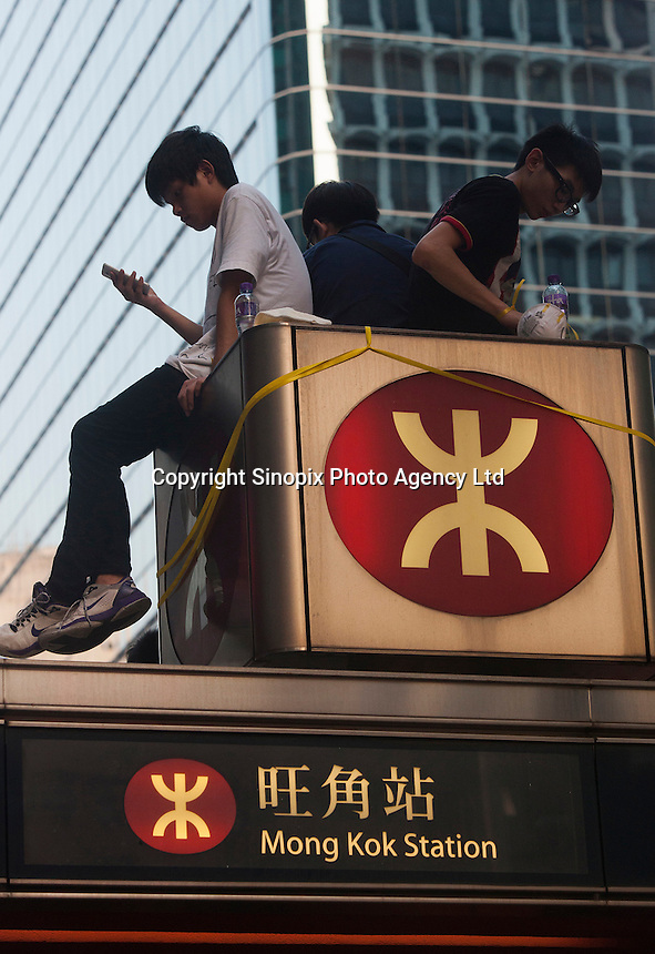 Pro-democracy protesters sit on top of a subway station in Mong Kok, on the second day of the mass civil disobedience campaign Occupy Hong Kong, Mong Kok, Kowloon, Hong Kong, China, 30 September 2014. The movement is also being dubbed the 'umbrella revolution' after the versatile umbrellas used to shield protesters from rain, sun - and police pepper spray.