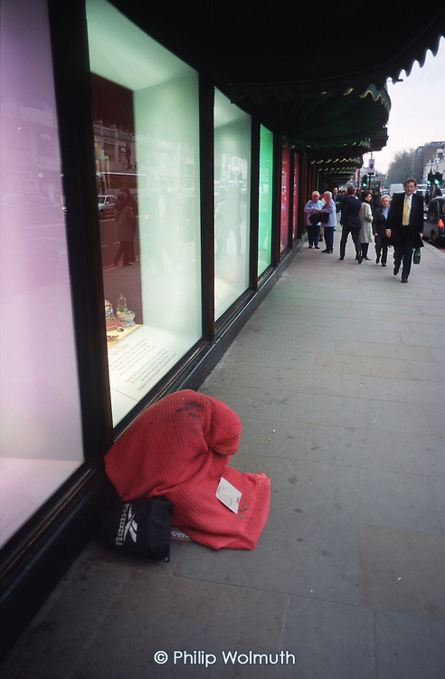A homeless man begs outside the luxury Harrods store in Knightsbridge, central London