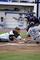 July 11, 2009:  Catcher Jonathan Jaspe of the Dunedin Blue Jays attempts to tag Tampa Yankees base runner Matt Cusick as home plate umpire Travis Carlson looks on during a game at Dunedin Stadium in Dunedin, FL.  Cusick was called safe and Jaspe was ejected for arguing the call.  Dunedin is the Florida State League High-A affiliate of the Toronto Blue Jays.  Photo By Mike Janes/Four Seam Images