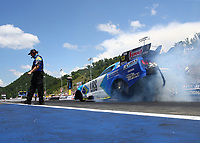 Jun 18, 2017; Bristol, TN, USA; NHRA funny car driver Tim Wilkerson does a burnout past crew chief Richard Hartman during the Thunder Valley Nationals at Bristol Dragway. Mandatory Credit: Mark J. Rebilas-USA TODAY Sports