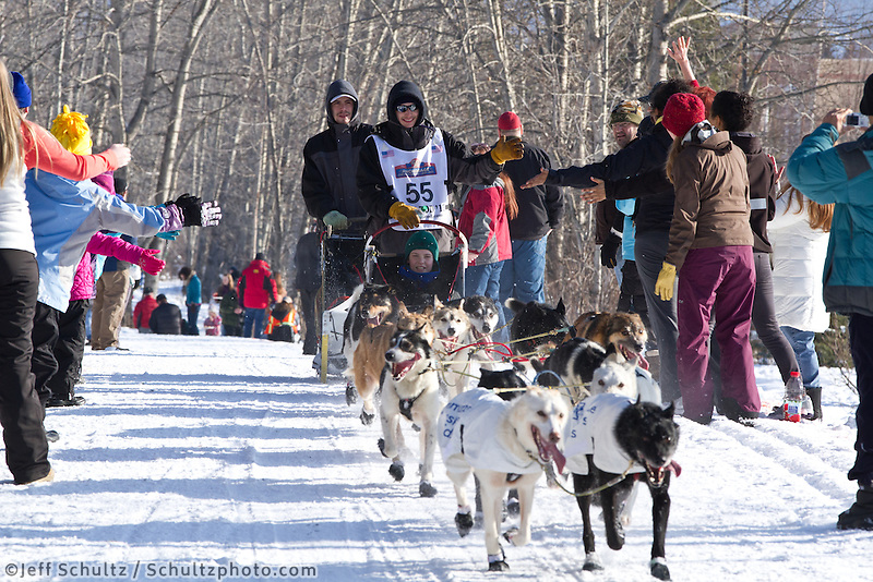 Josh Cadzow and team run past spectators on the bike/ski trail during the Anchorage ceremonial start during the 2013 Iditarod race.    Photo by Britt Coon/IditarodPhotos.com