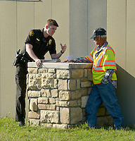 NWA Democrat-Gazette/BEN GOFF @NWABENGOFF<br /> A Springdale police officer interviews the driver of a semi truck that overturned on Monday Sept. 14, 2015 on White Road at the intersection with Elm Springs Road in Springdale. Matthew Thomas of Fayetteville was traveling South on White Road and was stopped waiting to make a right turn onto Elm Springs in a Dodge pickup truck. Thomas describes seeing the semi coming around a curve in the road, already beginning to roll as it approached his pickup. The semi clipped Thomas' pickup, causing minor damage, before rolling onto it's right side and sliding off the road.