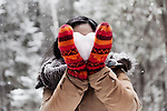 Young woman in red mittens holding a heart made of snow in front of her face, romantic concept