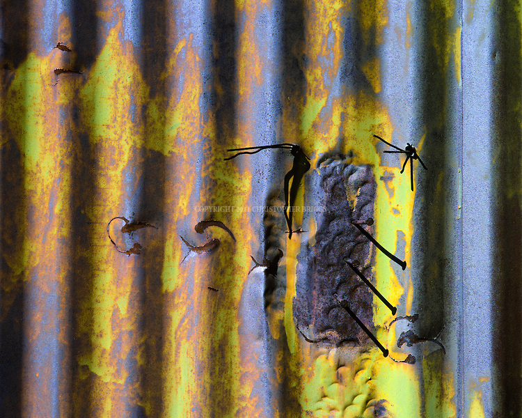 Nails protrude from a sheet of corrugated metal serving as a wall on a storage building in the southern California desert.