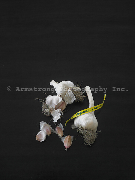 Garlic heads and cloves against a black background, with 'organically grown' label