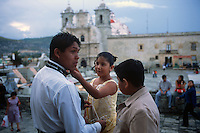 Family members prepare for a quinceañera celebration in Oaxaca, Mexico.
