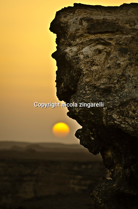 one massive rock coming off the shuwaymiyah plateau in southern oman. the sun about to set is in the background