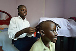 Martha Jacob braids the hair of her sister Nibit as the two prepare to go to school in Cairo, Egypt. The family fled violence in South Sudan, and today Martha and Nibit attend classes provided by St. Andrew's Refugee Services, which is supported by Church World Service.