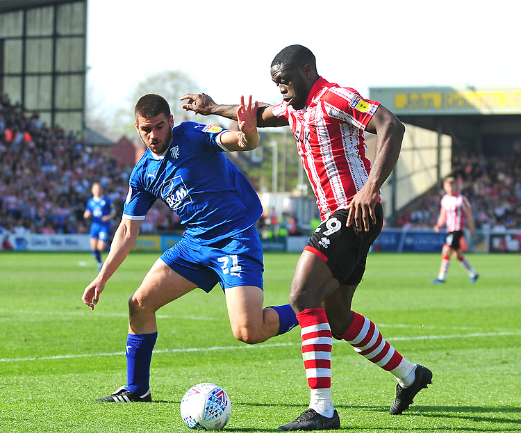 Lincoln City's John Akinde battles with Tranmere Rovers' Evan Gumbs<br /> <br /> Photographer Andrew Vaughan/CameraSport<br /> <br /> The EFL Sky Bet League Two - Lincoln City v Tranmere Rovers - Monday 22nd April 2019 - Sincil Bank - Lincoln<br /> <br /> World Copyright © 2019 CameraSport. All rights reserved. 43 Linden Ave. Countesthorpe. Leicester. England. LE8 5PG - Tel: +44 (0) 116 277 4147 - admin@camerasport.com - www.camerasport.com