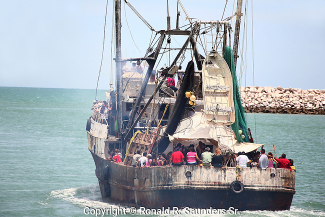Locals go for a joy ride on a commercial fishing boat along the Sea of Cortez during Mexico's annual Navy Day celebration