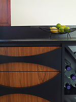 The kitchen units have a retro feel with their curved dark wood design.