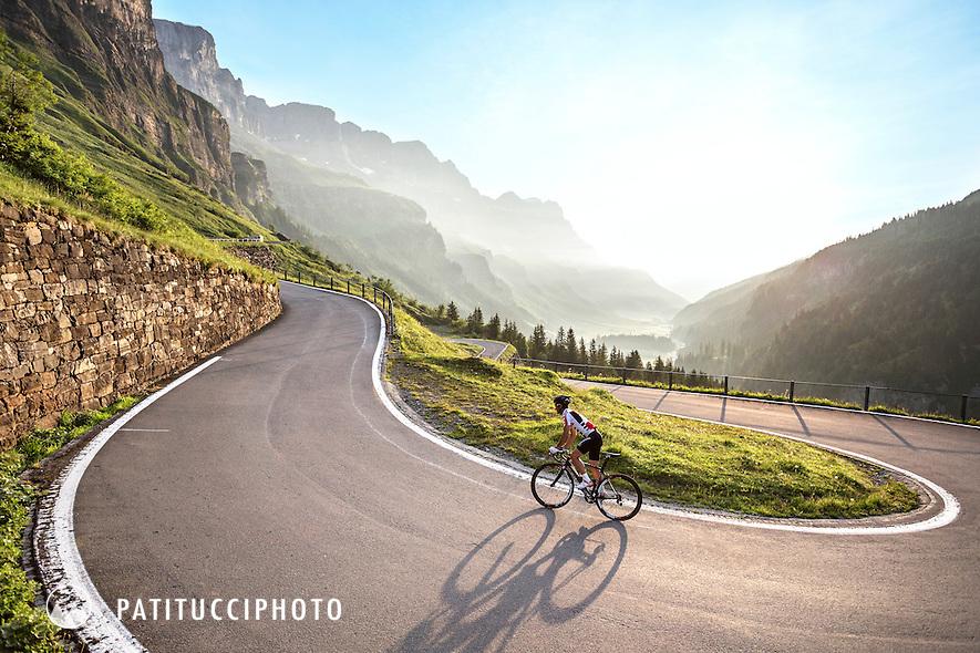 One man road biking uphill through a switchback on Switzerland's Klausen Pass