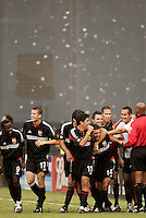 Teammates mob D.C. United's Ben Olsen after he scored in stoppage time to finish the scoring as D.C. United defeated the NY/NJ MetroStars 6 to 2 at RFK Stadium, Washington, D.C., on July 3, 2004.