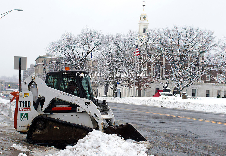 Waterbury, CT- 24 January 2015-012415CM02- A Bobcat removes snow from the sidewalk along Grand Street in Waterbury on Saturday.  According to the National Weather Service, Sunday is expected to be mostly sunny, with a high near 36F.  Christopher Massa Republican-American